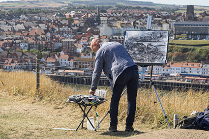 Robert on location at Whitby, North Yorkshire, drawing with charcoal mixed media – complexity simplified with focus and a keen eye for detail